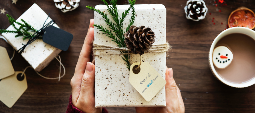 A white speckled box wrapped in twine and topped with a pinecone and some pine